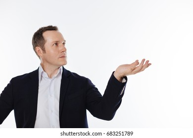 Careful mindful guy holding something in his hand