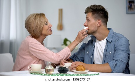 Careful mother wiping adult sons mouth during having tea at home, overprotection