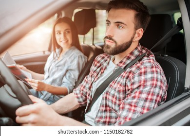 Careful and nice guy is driving car and looking straight forward. He is paying all of his attention to the road. Girl is sitting besides him. She is holding map and looking at young man with smile