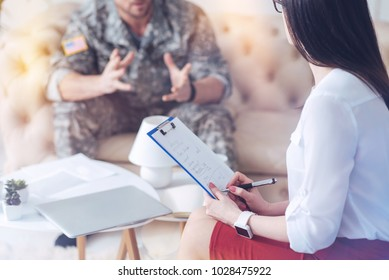 Careful psychological investigation. Close up of a young psychology holding a clipboard with notes and listening attentively to a soldier while making a diagnosis of a patient.
