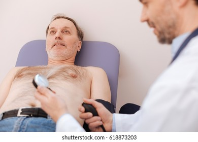 Careful qualified doctor doing patients blood pressure
