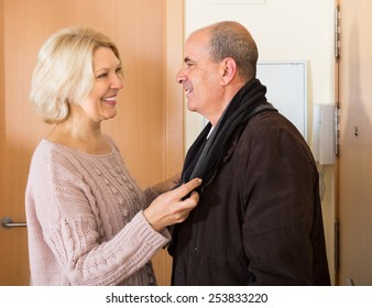Careful senior woman setting scarf on her elderly boyfriend and smiling at the doorway