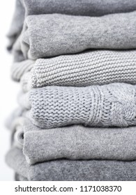 Careful stack of grey woolen and cashmere sweaters on white background. capsule wardrobe concept.