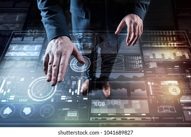 Careful work. Calm elegant professional programmer touching a futuristic transparent device while looking for the information about his client