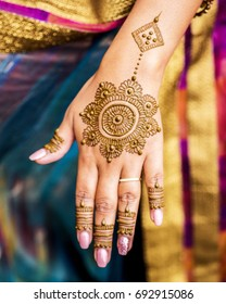 Carefully painted intricate design using henna, Mehndi art, on the hand of young Indian woman before a Vivaah-Indian Wedding. Background bokeh of wedding sari. Focus on hand.