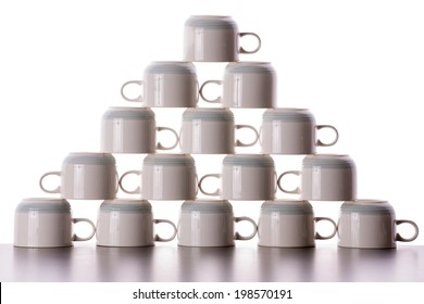 Carefully stacked pyramid of drying coffee cups with the handles facing in opposite directions in alternate rows in a fun decorative background pattern and texture
