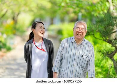 Caregiver and Asian senior male