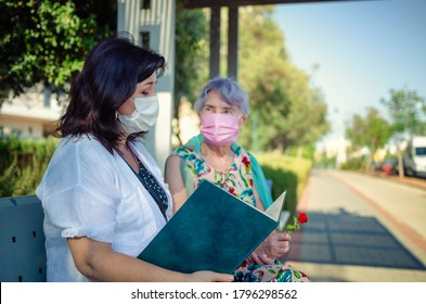Caregiver or attentive companion reading a book to an elderly client while sitting on a street bench. Both wear protective masks. The assistant's face is in focus. The old lady is slightly blurred.