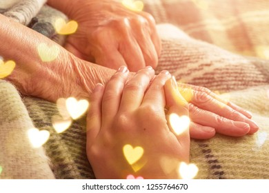 Caregiver, carer hand holding elder hand