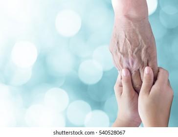 Caregiver, carer hand holding elder hand in hospice care. Philanthropy kindness to disabled old people concept.