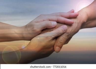 Caregiver, carer hand holding elder hand with sunset sky baackground. Philanthropy kindness to disabled concept.