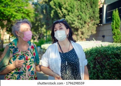 Caregiver or companion and senior adult woman speak in a friendly manner as they walk. Both are wearing protective face masks.