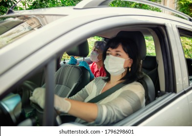 Caregiver drives her elder client to planned outings or events. Both wear protective masks. The face of the assistant is slightly blurred, the old woman is in focus.