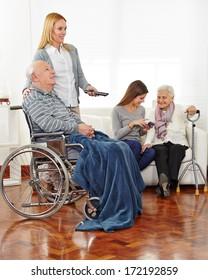 Caregiver entertaining senior citizens in a retirement home