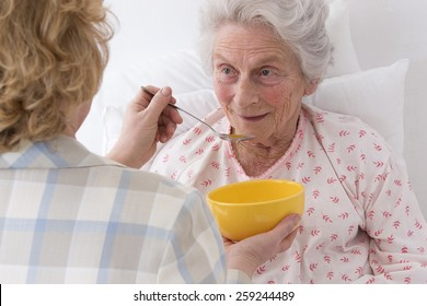caregiver  feeding an elderly woman at retirement house, or home