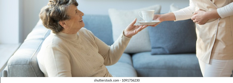 Caregiver giving a cup of tea to a smiling old lady during a stay in the hospice