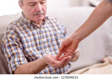 Caregiver giving the medicine to older male patient