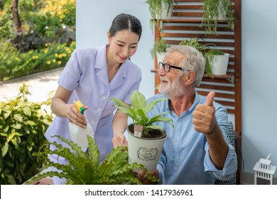 Caregiver help assist senior old man eldery puring water and taking care small tree on table thumb up