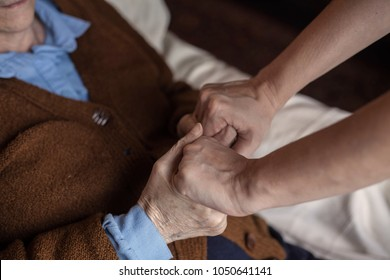 Caregiver helping elderly patient to get out of bed.