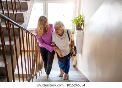 Betreuer, die älteren Frauen helfen, Treppe zu besteigen
