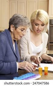 Caregiver helping a senior woman organize her prescription medicine into a daily pill organizer