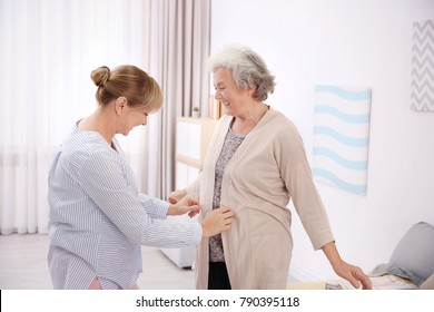 Caregiver helping senior woman to put on cardigan at home