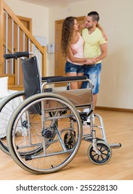 Caregiver helps handicapped girl to ambulate without invalid  chair. Focus on wheelchair