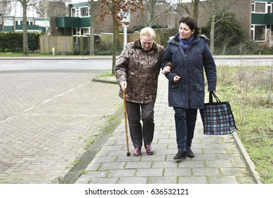 A caregiver helps an older woman with groceries