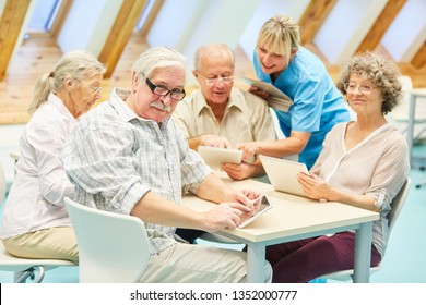 Caregiver helps seniors in the computer course with the Tablet PC and the Internet