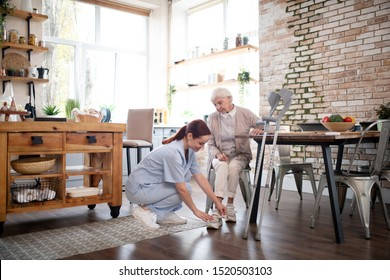 Caregiver lacing shoes. Hard-working caregiver wearing uniform lacing shoes for aged woman