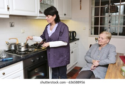 A caregiver is making soup for an elderly woman