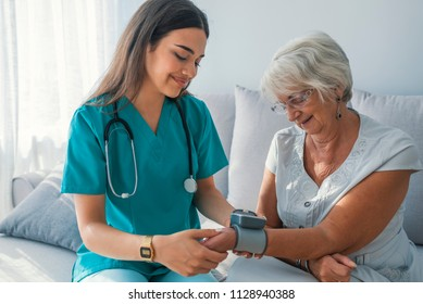 Caregiver measuring blood pressure of senior woman at home. Kind carer measuring the blood pressure of a happy elderly woman in bed in the nursing home.