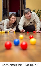 caregiver and mentally disabled woman playing with balls, alternative learning