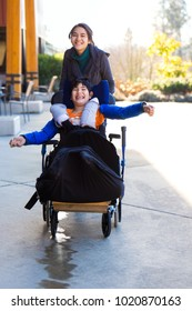Caregiver pushing young disabled boy in wheelchair and running together outside