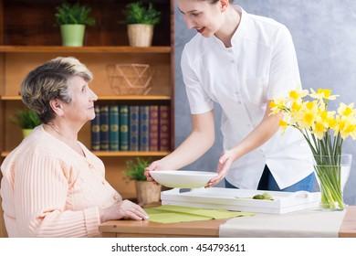 Caregiver serving nutritious soup to senior lady