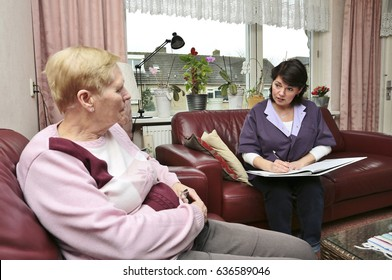 A caregiver speaks with an elderly woman