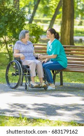 Caregiver talking to disabled senior woman in wheelchair outdoors in summer park.