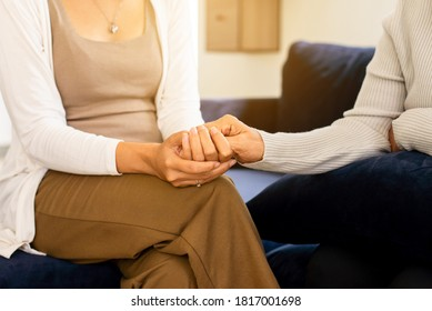 Caregiver woman holding hands to elderly with alzheimer disease at home,Adult social care concept