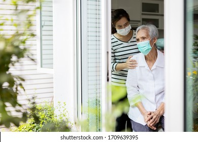 Caregiver woman take care of the elderly,depressed senior is waiting for her family to visit at home,social distancing,nostalgia,stress,life depression,stay home during Covid-19,Coronavirus pandemic