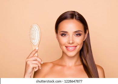 Careless carefree beautiful lovely pretty dreamy lady with her hollywood teeth toothy smile naked shoulders she holds comb look at camera make white smile isolated on pastel beige background