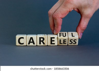 Careless or careful concept. Male hand flips wooden cubes and changes the word 'careless' to 'careful'. Beautiful grey background, copy space.