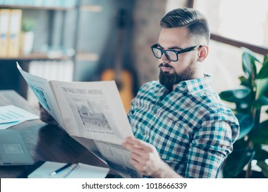 Careless concentrated clever bearded guy clothed in casual checkered shirt is reading a newspaper at work, he has a break, he is sitting at the table