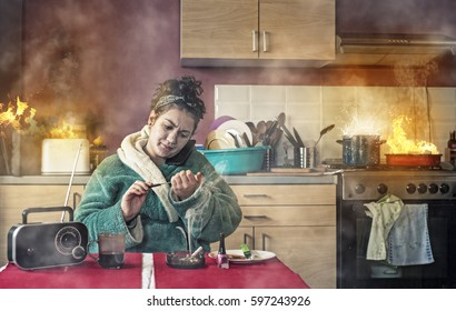 Careless girl talking on phone and makinger her nails while the kitchen is on fire.