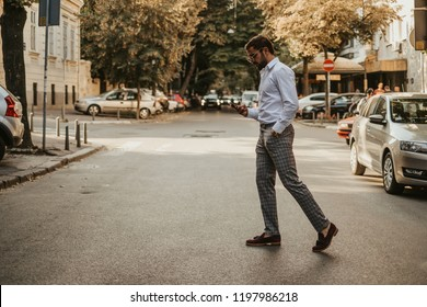 Careless handsome man with hand in his pocket looking at mobile phone while crossing the street