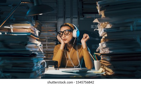 Careless lazy female employee sitting at office desk and listening to music instead of working, she is surrounded by piles of paperwork