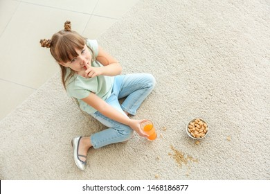 Careless little girl eating nuts and drinking juice while sitting on carpet