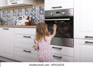 careless naive child girl touches hot glass door of oven in the kitchen