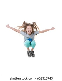 Careless preteen with long hair, having fun and leaping up high, isolated on white background