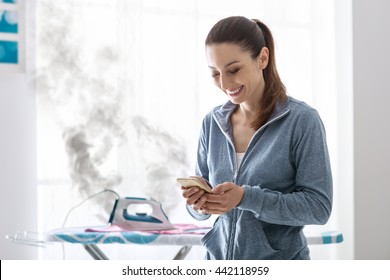 Careless smiling housewife at home texting with her smartphone, she has left the iron on the ironing board