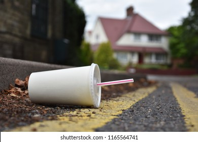 A carelessly discarded drink or soda container with drinking straw lies in the gutter of an urban street